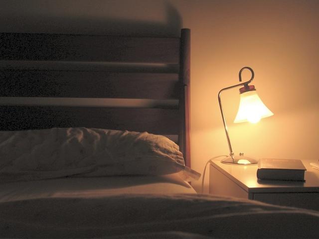 Posteľ, vankúš a nočný stolík so zapálenou lampou.jpg