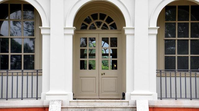 Biele vchodové dvere so sklenenou výplňou na rodinnom dome a veľké okná.jpg