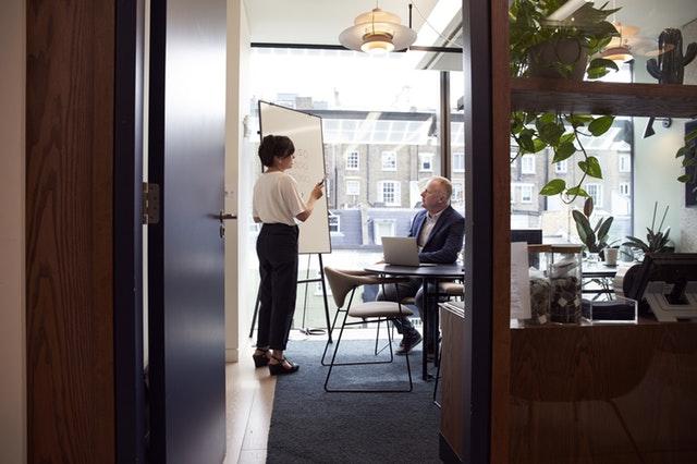 Žena muž v kancelárii s veľkou presklenou stenou.jpg
